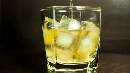 lento : Whisky is poured over ice in slow motion