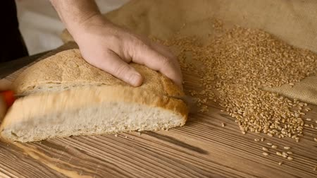 slicer : Cut slice of bread on the wooden table, in slow motion, close up