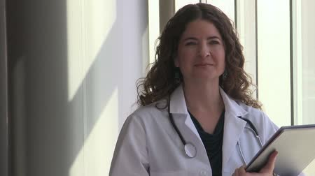 phd : A female doctor, with long brown hair possibly in her late 20s is in her office standing by a window. Stock Footage