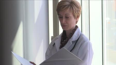 phd : A female doctor is in her office standing by a window thinking about a case.