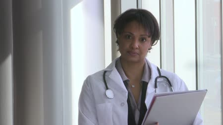 phd : A young female African American doctor standing in her office with a chart and a stethoscope around her neck