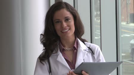 醫療保健 : A brunette female doctor, possibly in her mid 30s is holding a medical chart.  She turns and faces the camera with a confident smile.