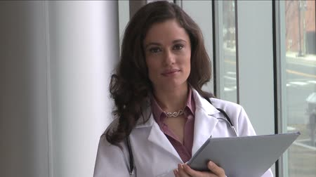 egészségügy és az orvostudomány : A brunette female doctor, possibly in her mid 30s is holding a medical chart.  She turns and faces the camera with a confident smile.