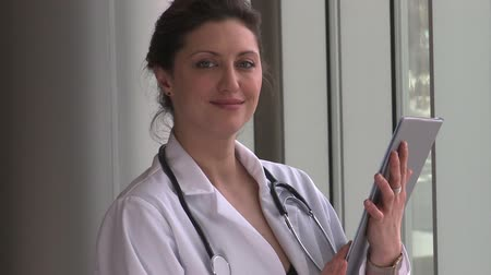 physicians : A female doctor,with brown hair, possibly in her early 30s is holding a medical chart.  She turns and faces the camera with a happy expression.