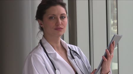 phd : A female doctor,with brown hair, possibly in her early 30s is holding a medical chart.  She turns and faces the camera with a serious look. Stock Footage