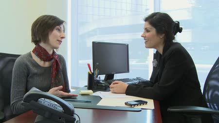 сплетни : Two female coworkers have a friendly discussion in the office. Стоковые видеозаписи