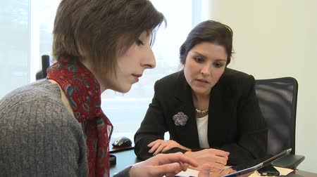 gyűlés : Two female coworkers review a presentation on a tablet computer.