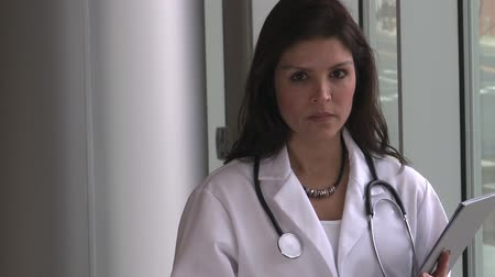 przywództwo : A brunette female doctor, possibly in her early 40s turns and faces the camera.  She has a serious expression on her face.