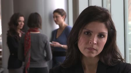 pletyka : A brunette female possibly in her early 40s turns and glares at the camera, while her coworkers talk in the background. Stock mozgókép