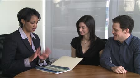 mls : A young couple discusses possibilities with their real estate agent. Stock Footage