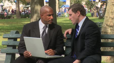 ethic : Two business men discuss the details of an upcoming presentation in the informal setting of the park.