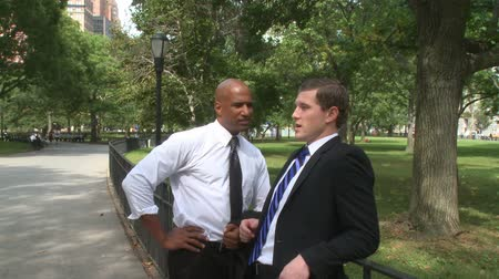disputa : Two young businessmen hold an informal conversation in a city park. Vídeos