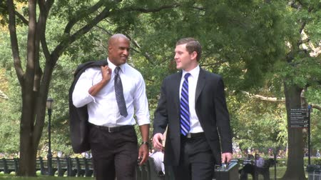 ethic : Two young businessmen while walking through a city park. Stock Footage