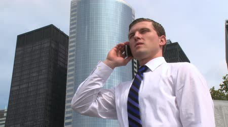 ethic : A young businessman talks on a cell phone with city buildings in the background
