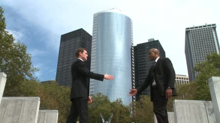 disputa : Two men meet and shake hands in front of several skyscrapers.