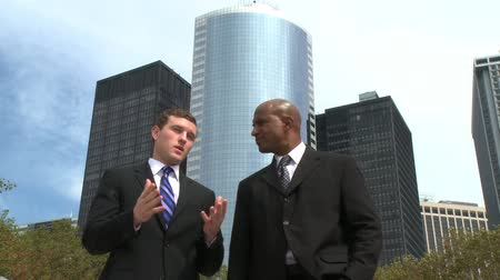 ethic : Two men meet and shake hands in front of several skyscrapers.
