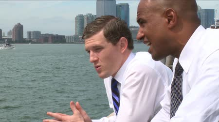 ethic : Two young professionals have an informal conversation at the waterfront.