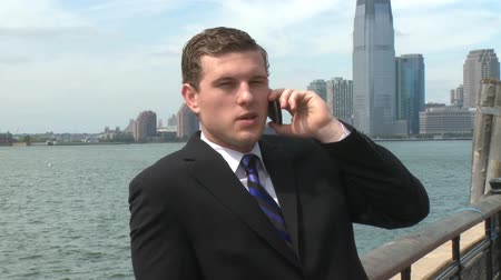 optymizm : A young businessman has a conversation on his cell, while standing near the waterfront.
