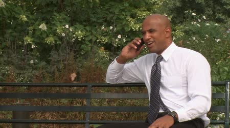 ethic : A young professional talks on a cell phone in a city park.