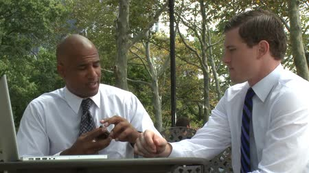 ethic : Two professionals sit at a park cafe and discuss an important presentation.