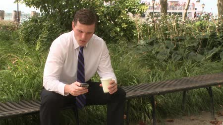 disputa : A young professional talks on a cell phone in a city park.