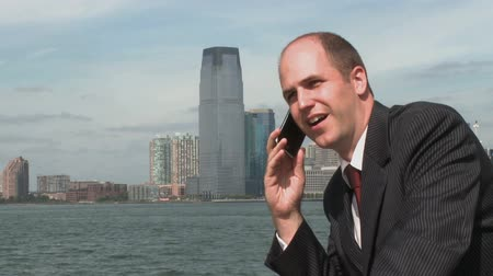 ethic : A young businessman has a conversation on his cell, while standing near the waterfront.