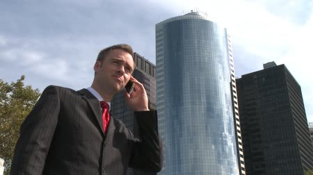 disputa : A young businessman talks on a cell phone with city buildings in the background