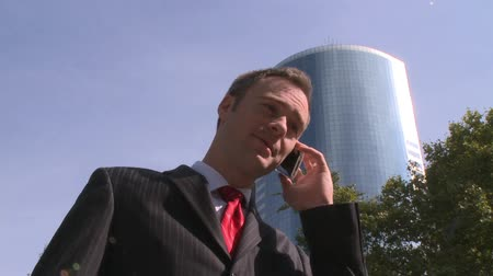 trabalho em equipe : A young businessman talks on a cell phone with city buildings in the background