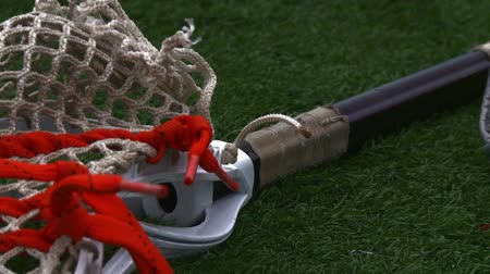 cricket pads : Lacrosse equipment laying on the field Stock Footage
