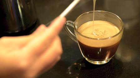xícara de café : pouring the sweetened condensed milk into the coffee mocha
