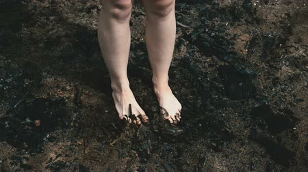 Girl tramples on the scorched earth with her feet Vídeos