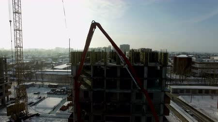 Crane with cement slurry rises to the building on the construction site