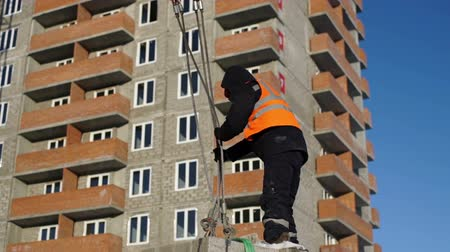 Man unties the ropes on the stone blocks outdoor