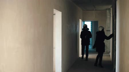 Guy and the girl are walking along the corridor of the house under construction Stock Footage