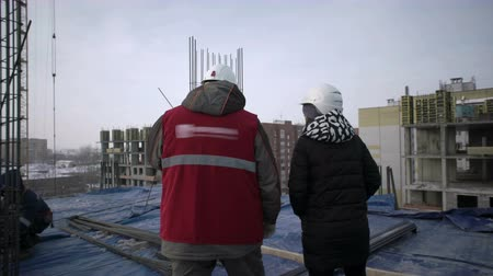 Brigadier with a woman are walking on the roof of a house under construction