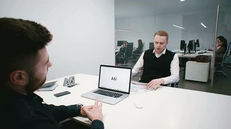 Two managers discuss the details of the project in the office of the company