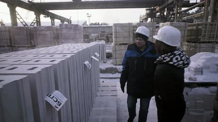 Women walk past the building material and talk