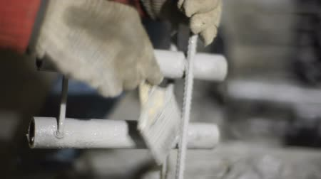 Worker paints a metal tube close up
