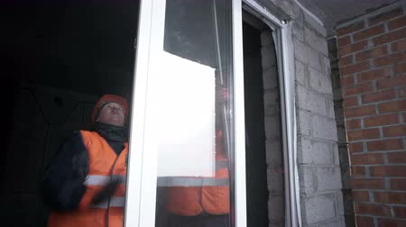 Workers place the glass in the plastic frame of the window in the building