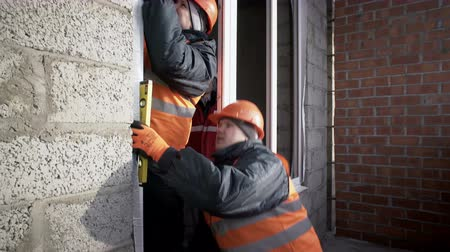 Workers checks the walls of the house on irregularities close up