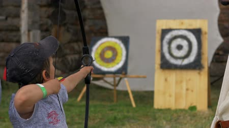 tiro com arco : Little boy shoots an arrow and misses close up Stock Footage