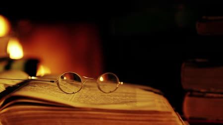 rustik : Old book and glasses in front of the fireplace. Vintage style.Shallow depth of field.