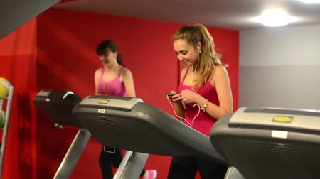 tornaterem : Young women doing sports, running on machines in fitness, gym. Workout. Woman listening to music.