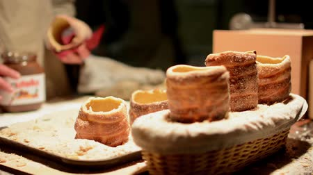 дымоход : Trdelník (chimney cake or stove cake) in shop (in night) - man in the background spread cake with hazelnut cream