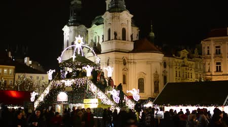cseh : Christmas marketplace (shops) with people on the square - with shining decorations - Old Town Square - in background historical building - in night Stock mozgókép
