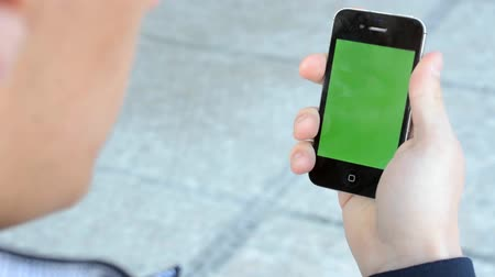 smartfon : A man looks at the smartphone - green screen
