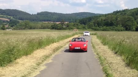 obec : Man and woman travel in a convertible car on the road - nature in the background