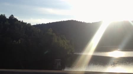 fast ride over the bridge with sun rays - lake with forest in the background - sunset