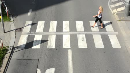 pedestre : woman goes across the street (pedestrian crossing) - view from above
