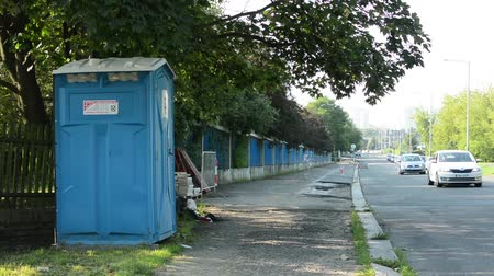 уборная : modern latrine next to the road in the city - passing cars - city in background - trees in foreground Стоковые видеозаписи